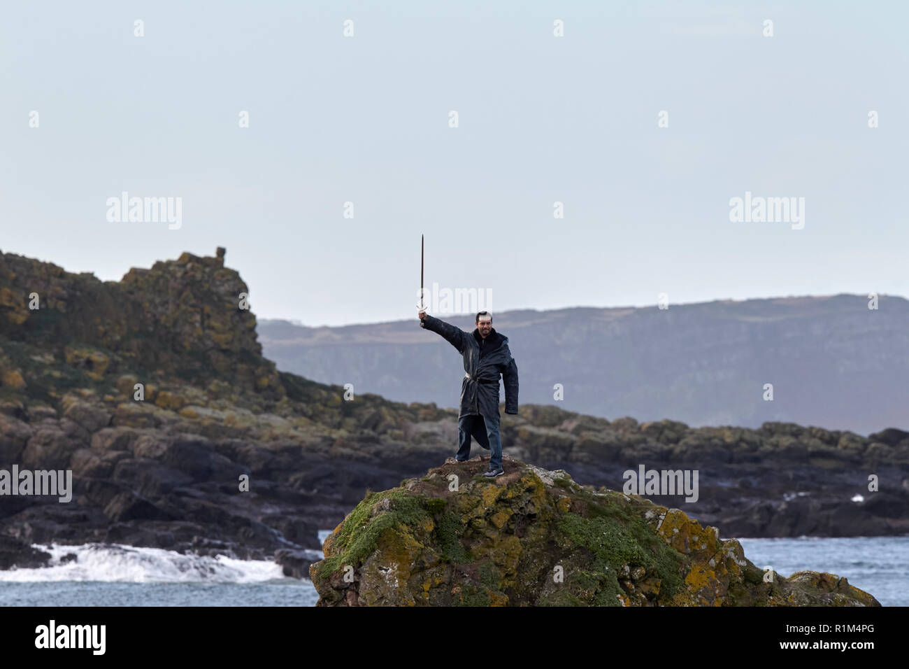 male Tourist wearing costume holding sword aloft standing on rocks on a Game of Thrones guided coach tour in Ballintoy on Northern Irelands north coas - Stock Image