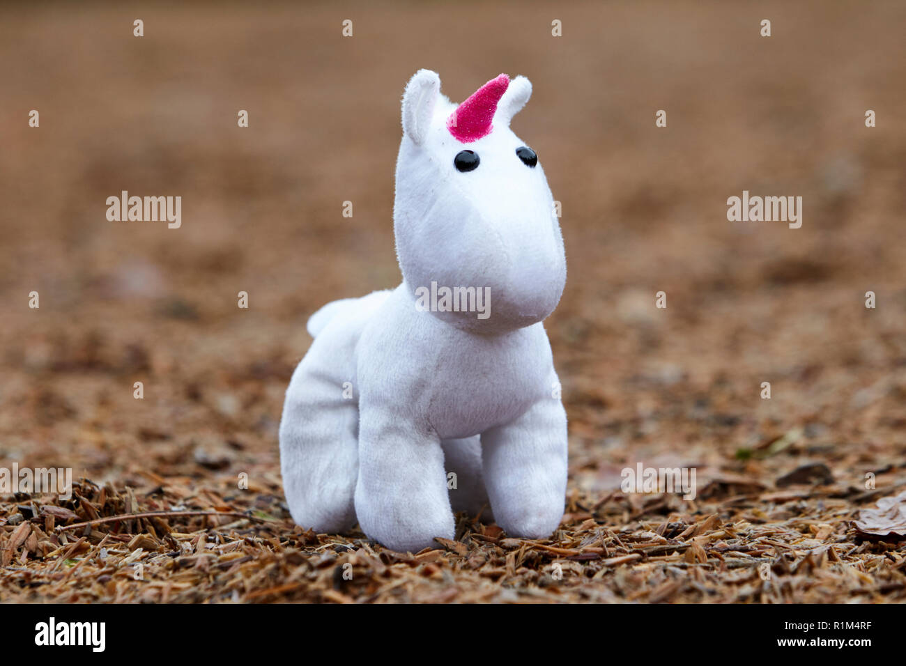 Little girl childs soft toy unicorn lost in a childrens playground - Stock Image
