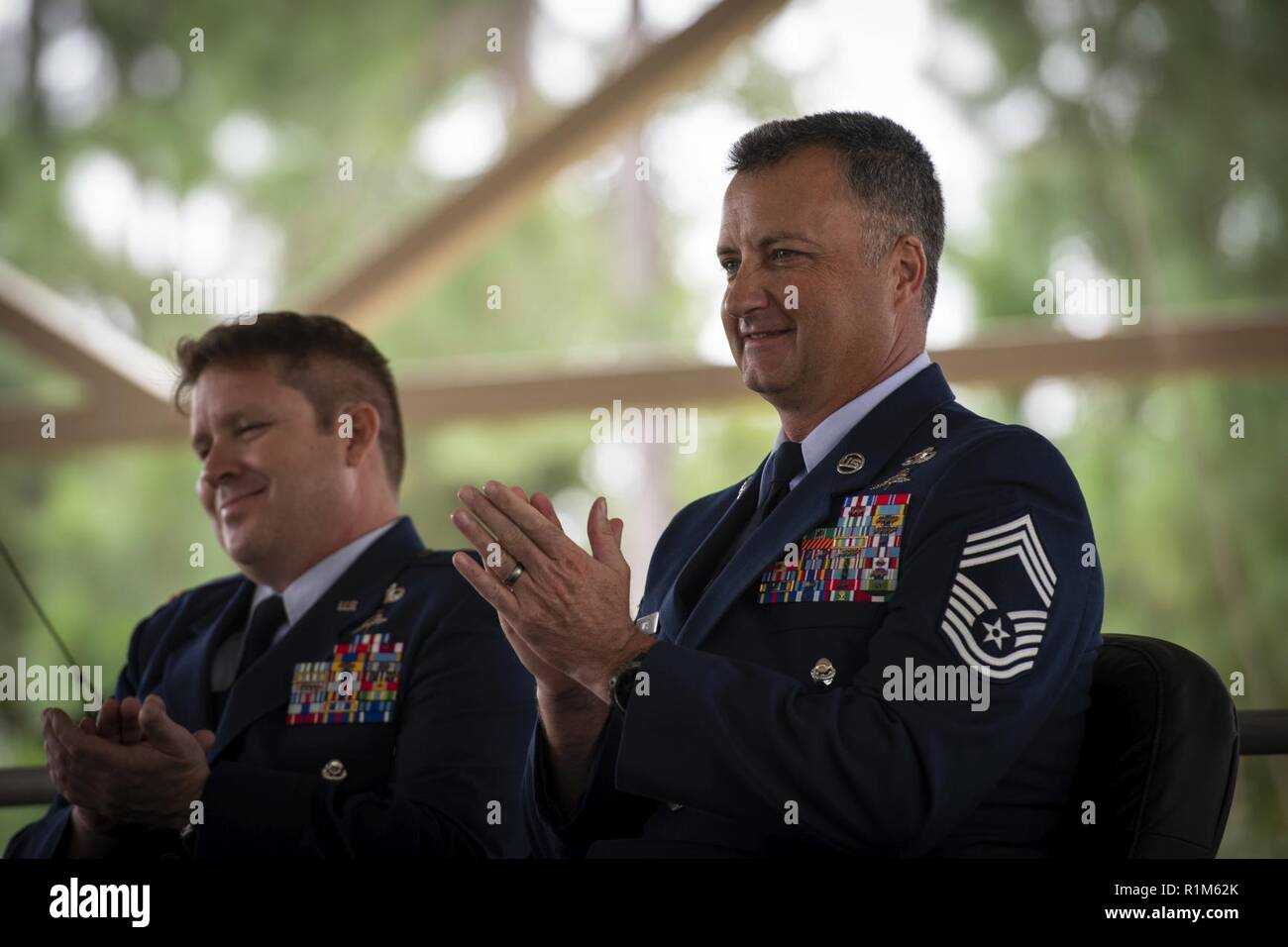 Chief Master Sgt. Michael West, right, a special tactics combat controller with the 24th Special Operations Wing, applauds during his retirement ceremony at Hurlburt Field, Florida, Oct. 19, 2018. For 30 years, West was actively engaged in nearly every operation with a U.S. presence, beginning with Operation DESERT STORM to the more recent Operations FREEDOM SENTINEL and RESOLUTE SUPPORT in Afghanistan. - Stock Image