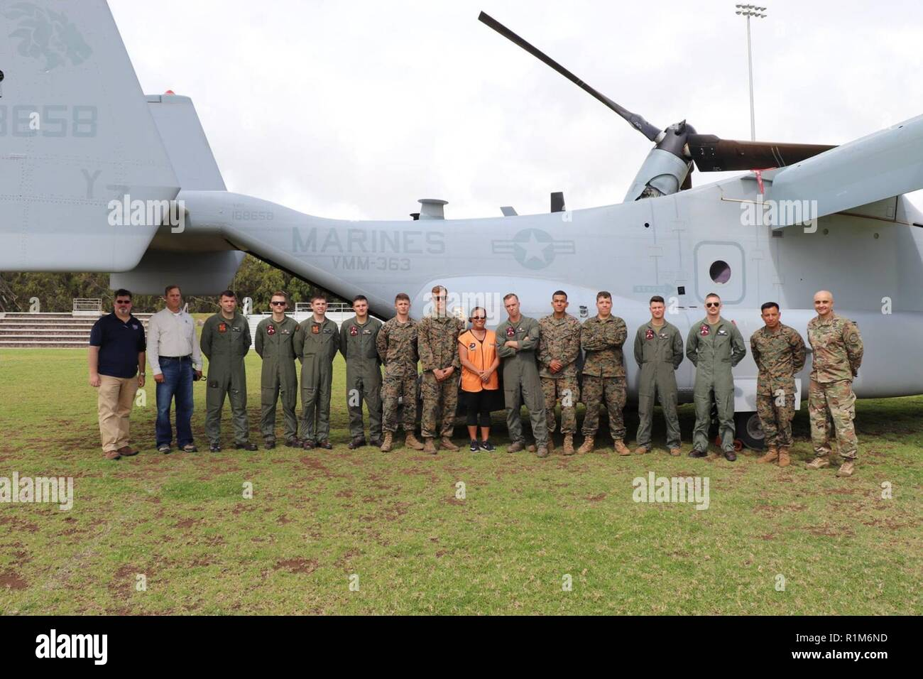 """U.S. Army Garrison Pohakuloa leadership and U.S. Marines with the Marine Medium Tiltrotor Squadron, VMM-363, nicknamed the """"Lucky Red Lions,"""" from Marine Corps Base Hawaii stand in front of the MV-22B Osprey aircraft before the Waimea Fall Festival, at the Waimea District Park. Stock Photo"""