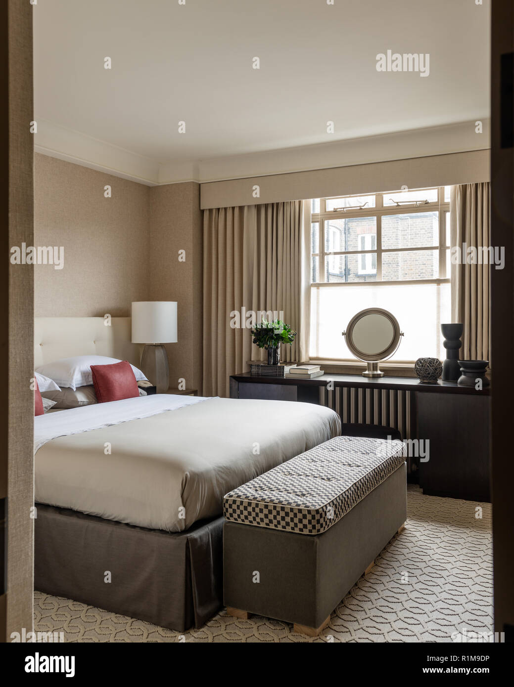 Modern bedroom with dressing table by window - Stock Image