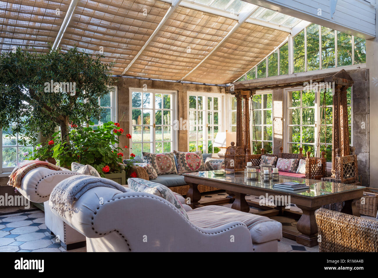 Conservatory dining room with sofas - Stock Image