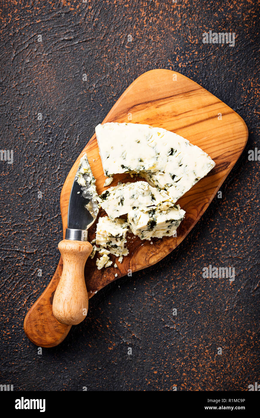 Blue cheese and knife on cutting board - Stock Image
