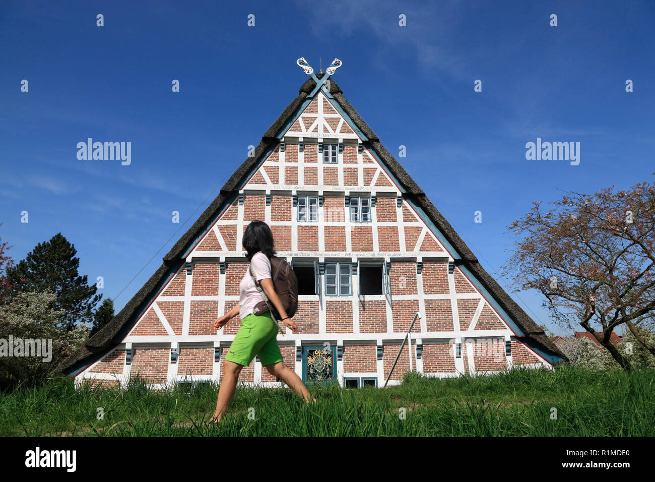 Hiker in front of an Old Farmhouse at Este-dike, Jork-Koenigreich, Altes Land, Lower Saxony, Germany, Europe - Stock Image
