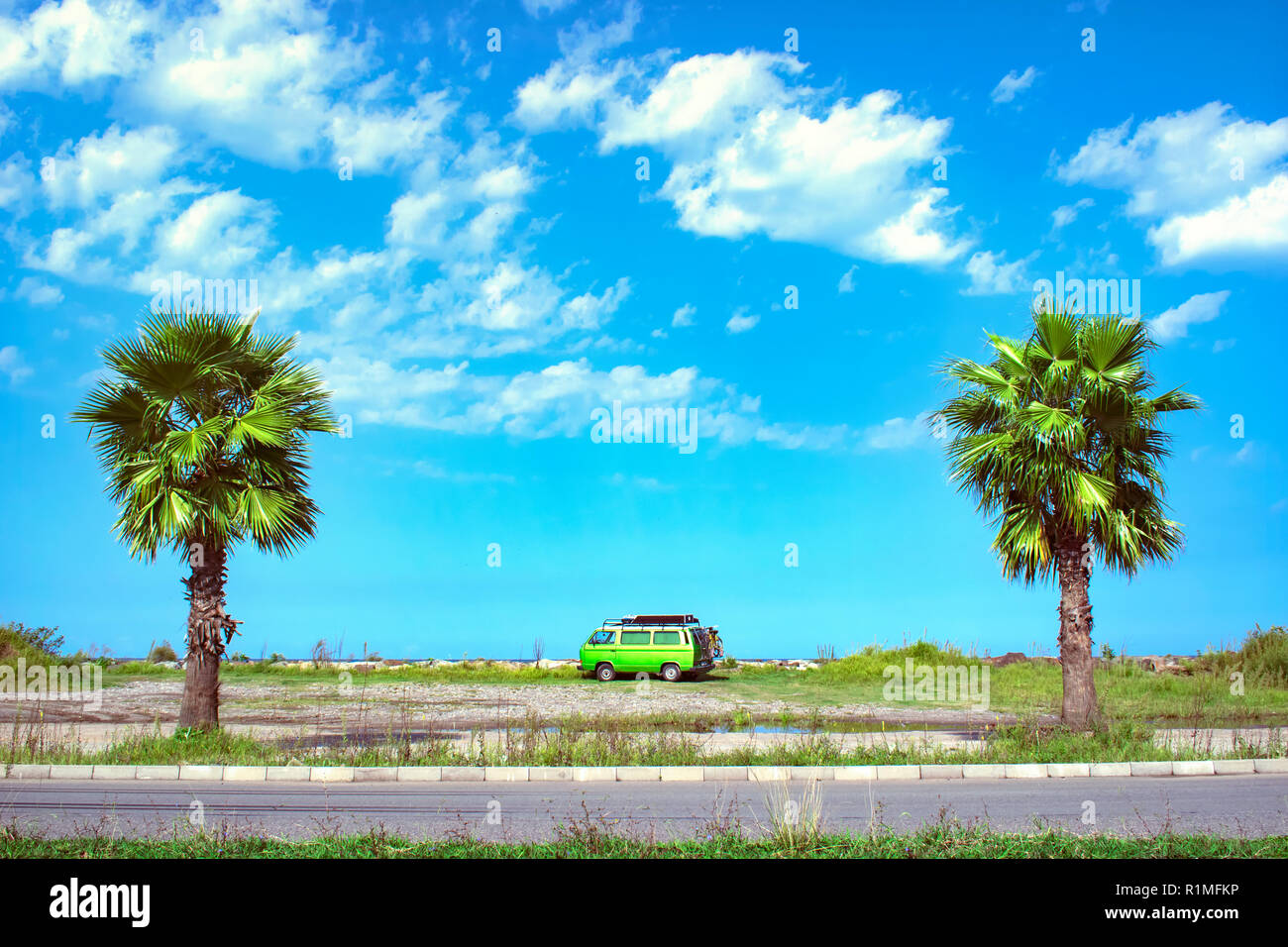 Fully equipped old timer camper van parked on the beautiful long beach between two palm trees on a bright sunny summer day Stock Photo