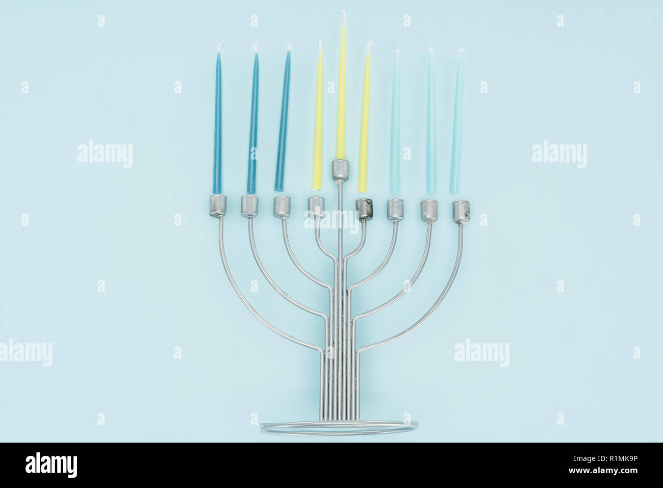 top view of menorah and candles on blue background, hannukah celebration concept - Stock Image