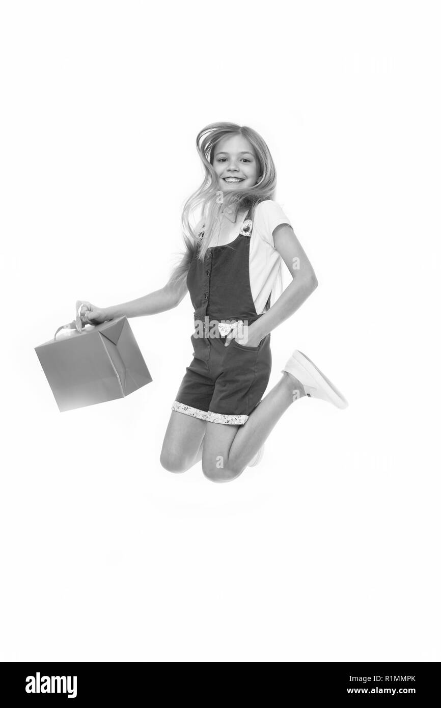 Finally bought it. Girl cute teenager carries shopping bag while jumping. Sale benefits. Kid bought clothing summer sale. Seasonal sale concept. Girls absolutely fond of shopping. - Stock Image