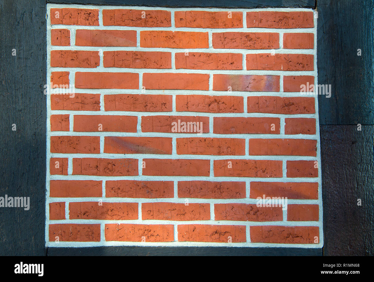 Brickwork of red bricks on wooden wall on black background. Defense, protection, security concept - Stock Image