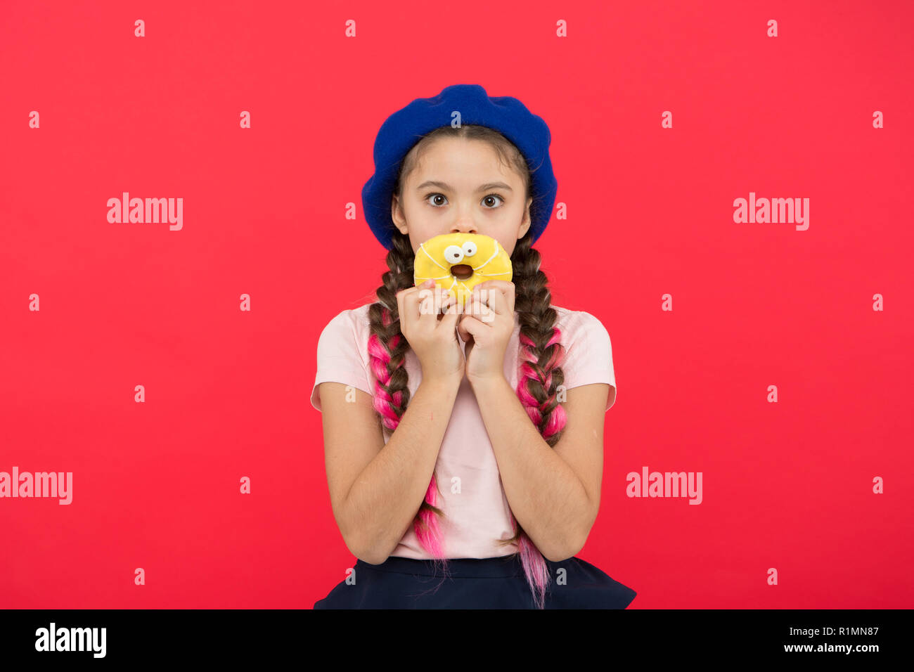 Impossible to resist fresh made donut. Girl hold glazed cute donut in hand red background. Kid smiling girl ready to eat donut. Sweets shop and bakery concept. Kids huge fans of baked donuts. - Stock Image