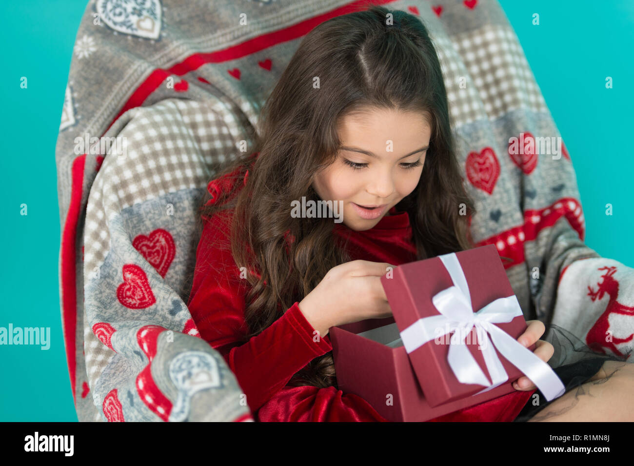What is inside. Happy little smiling girl open new year gift box. Cute little child girl with new year present. Festive celebration of the New Year Eve at home. Merry Christmas and Happy New Year. - Stock Image