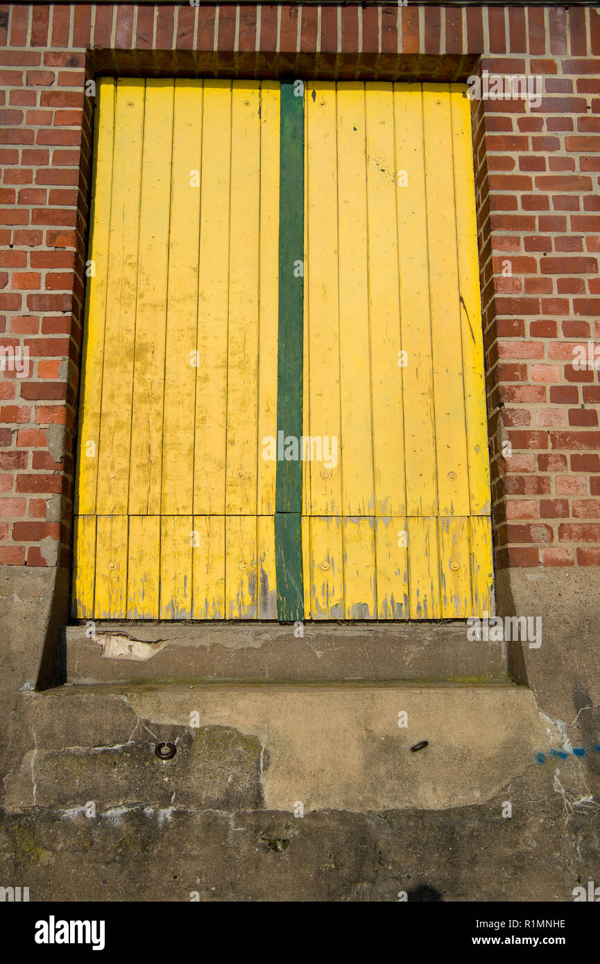 Portal, window or door shut with yellow wood planks in derelict building on red brick wall background. Refusing, rejecting, decay concept - Stock Image