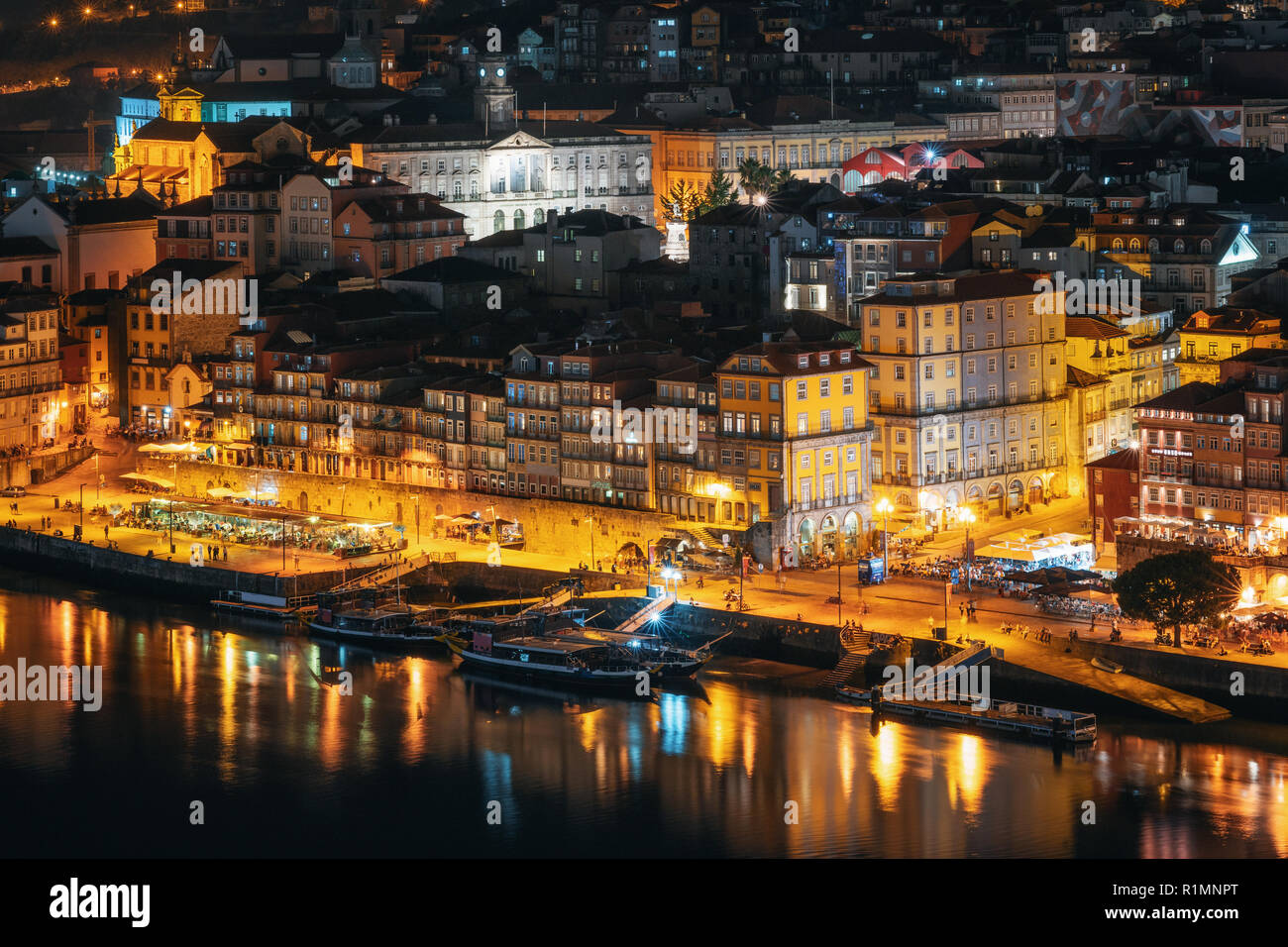Porto cityscape. Embankment Douro River with bars, restaurants and active nightlife at night, Portugal - Stock Image
