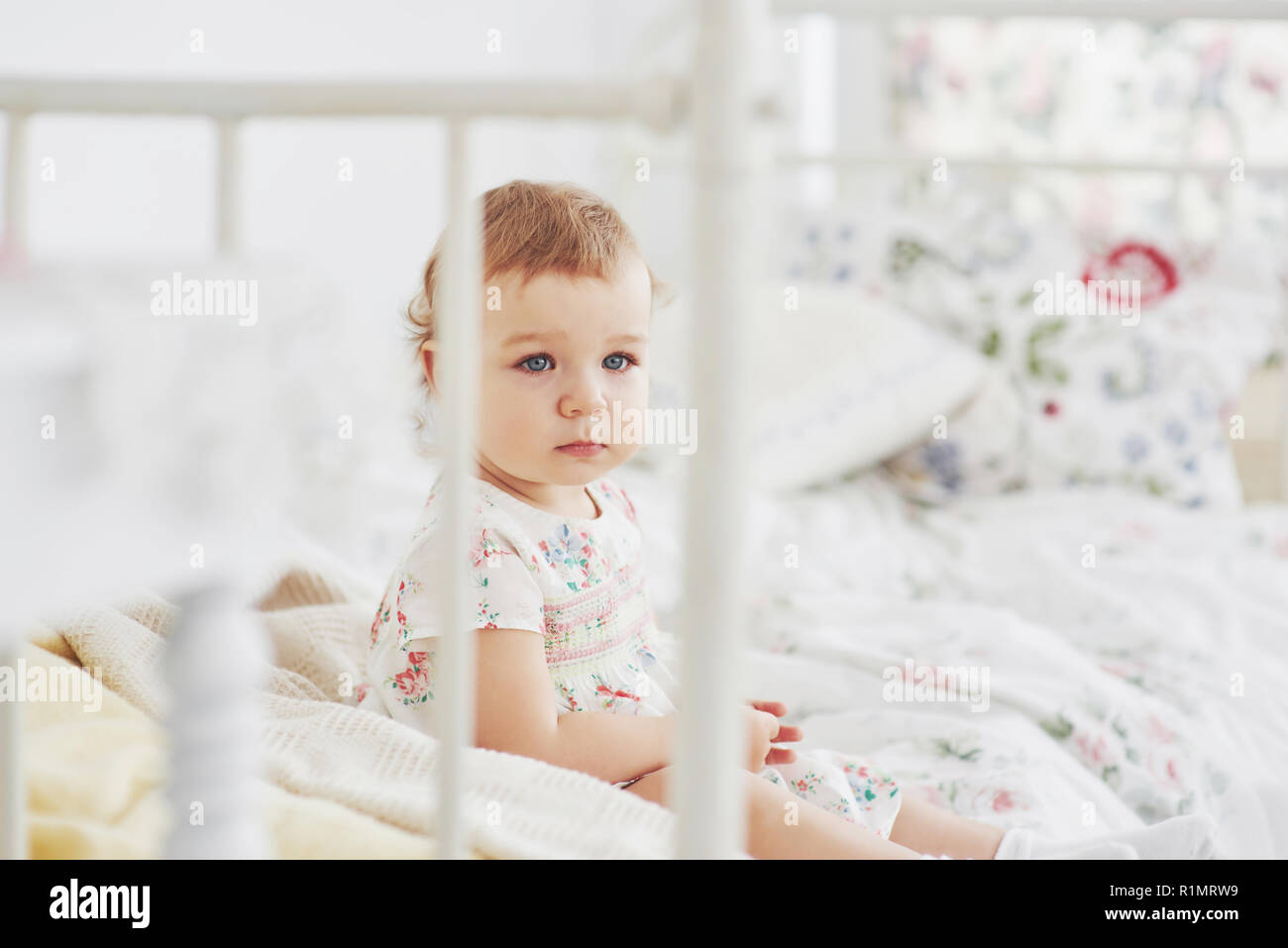 Childhood concept. baby girl in cute dress siting at bed playing with toys by the home. White vintage childroom - Stock Image