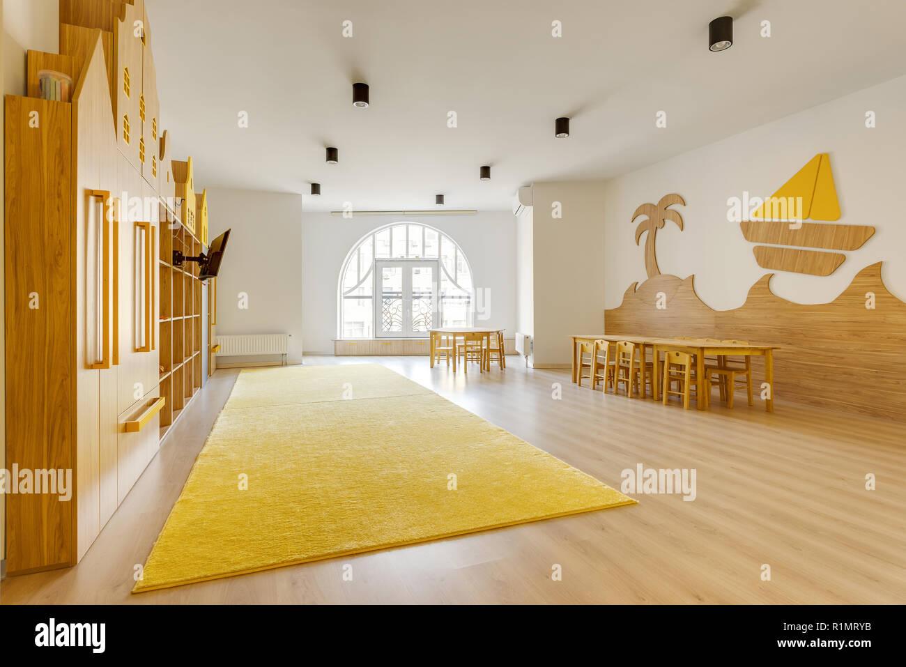 Cozy light classroom with wooden furniture in modern kindergarten