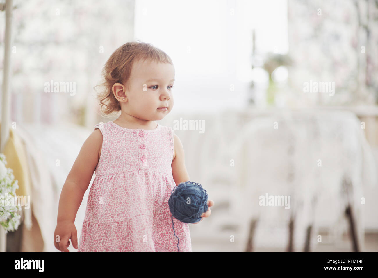 Childhood concept. Baby girl in cute dress play with colored thread. White vintage childroom - Stock Image