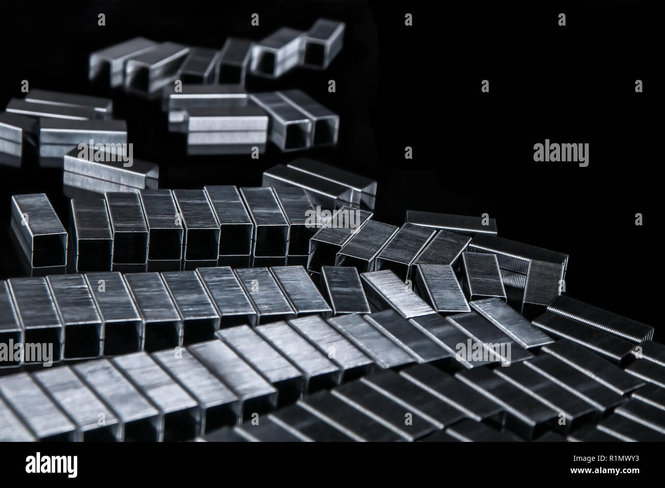 Many metallic refills staples on modern black work desk - Organizing and office attachment supply for writing, paper documents, research and studying - Concept of school, education, secretary, university and learning - Stock Image