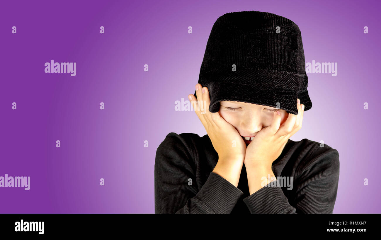closeup of young boy in black shirt and black hat with shy, vulnerable and ticklish expression - Stock Image