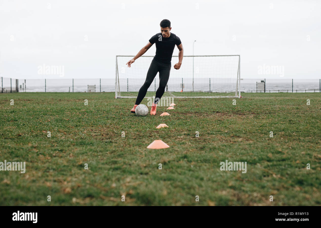 Footballer doing cone dribbling drill on field. Footballer moving the ball in between the cones practicing dribbling. - Stock Image