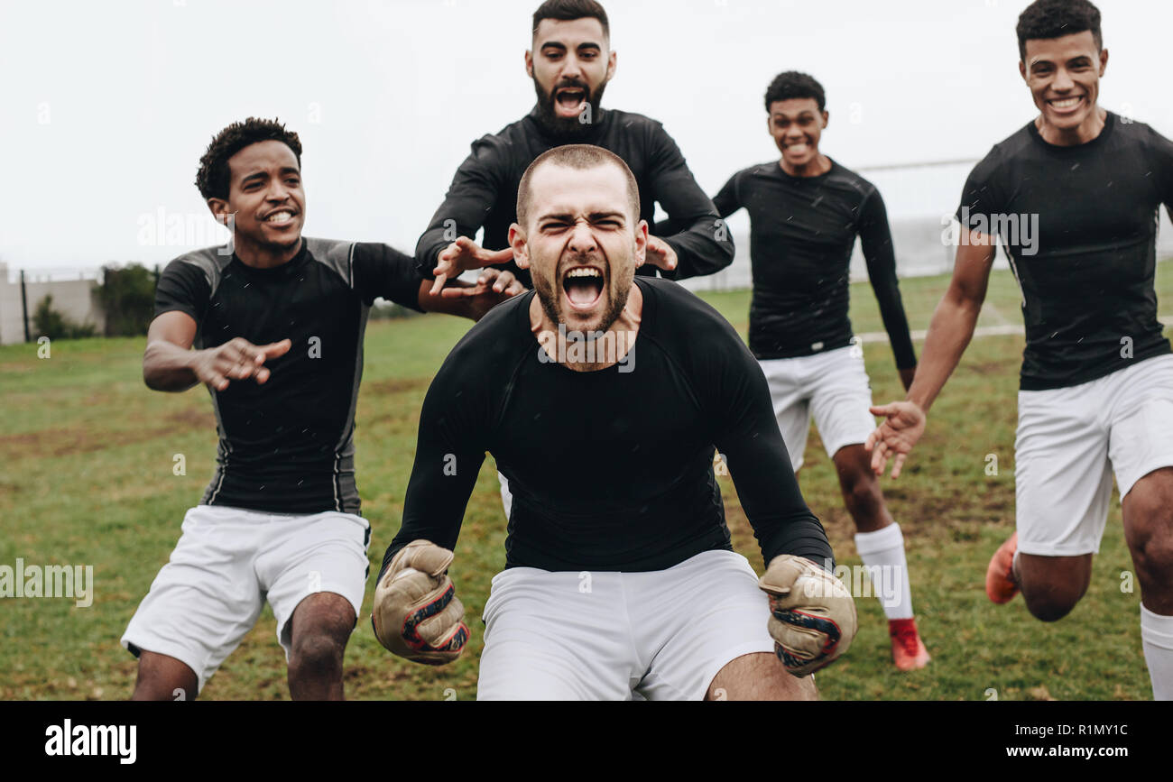 Goalkeeper doing a knee slide in excitement after winning the match. Soccer teammates celebrating success screaming in joy on the field. - Stock Image