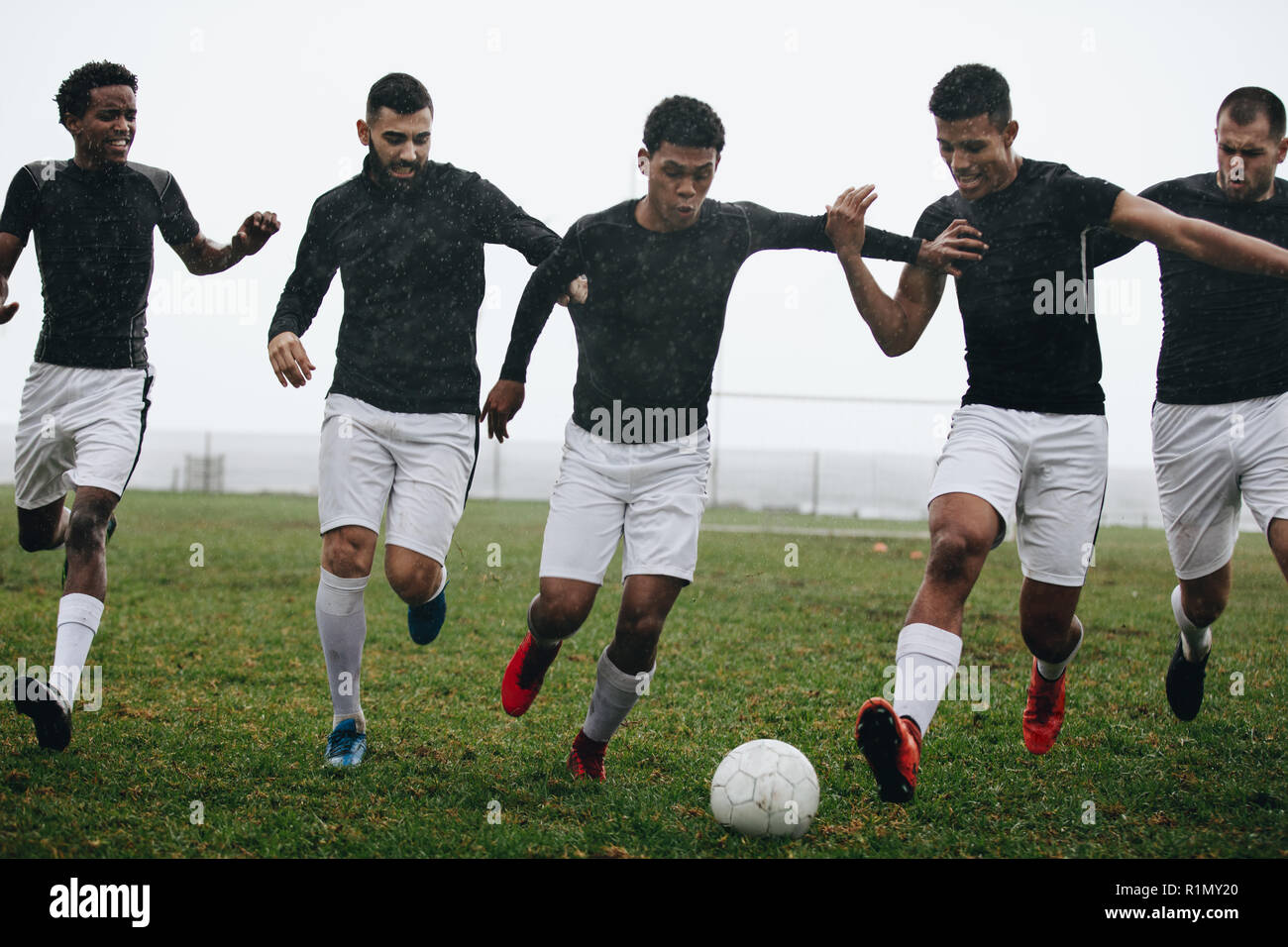 Men playing soccer running after a football on a rainy morning. Footballers trying to take possession of the ball running on the field playing soccer. - Stock Image