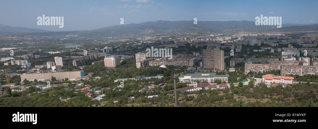 Panoramic view of the city of Tbilisi in Georgia showing old soviet tower blocks and mountains behind. Seen from the Chronicle of Georgia. - Stock Image