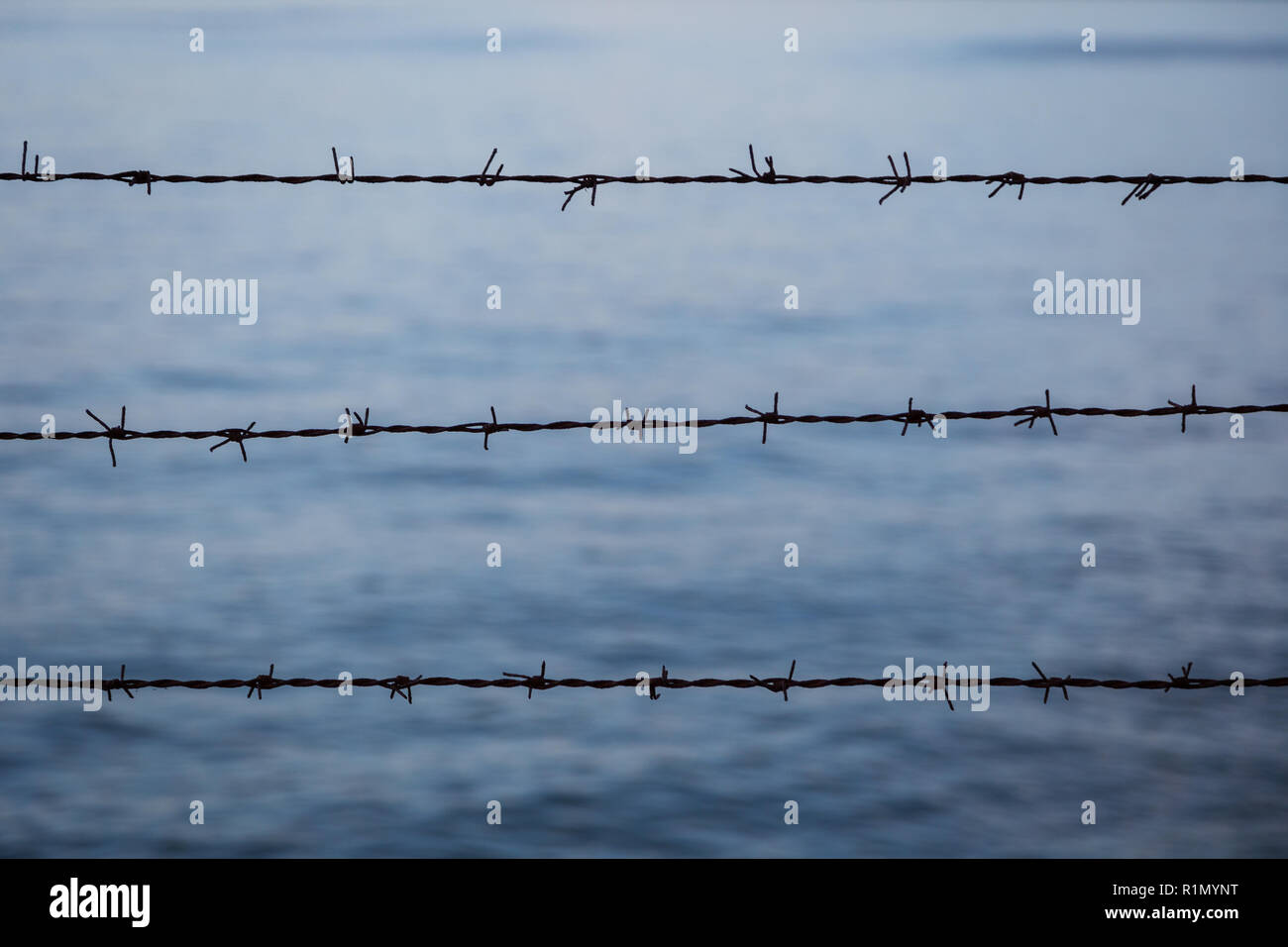 Silhouette of barbed wire fence against blurry blue water in the evening. Focused on the foreground. - Stock Image