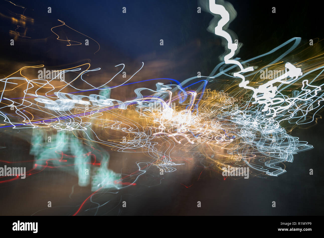 Abstract photo of motion and colorful light trails in a city at night. - Stock Image
