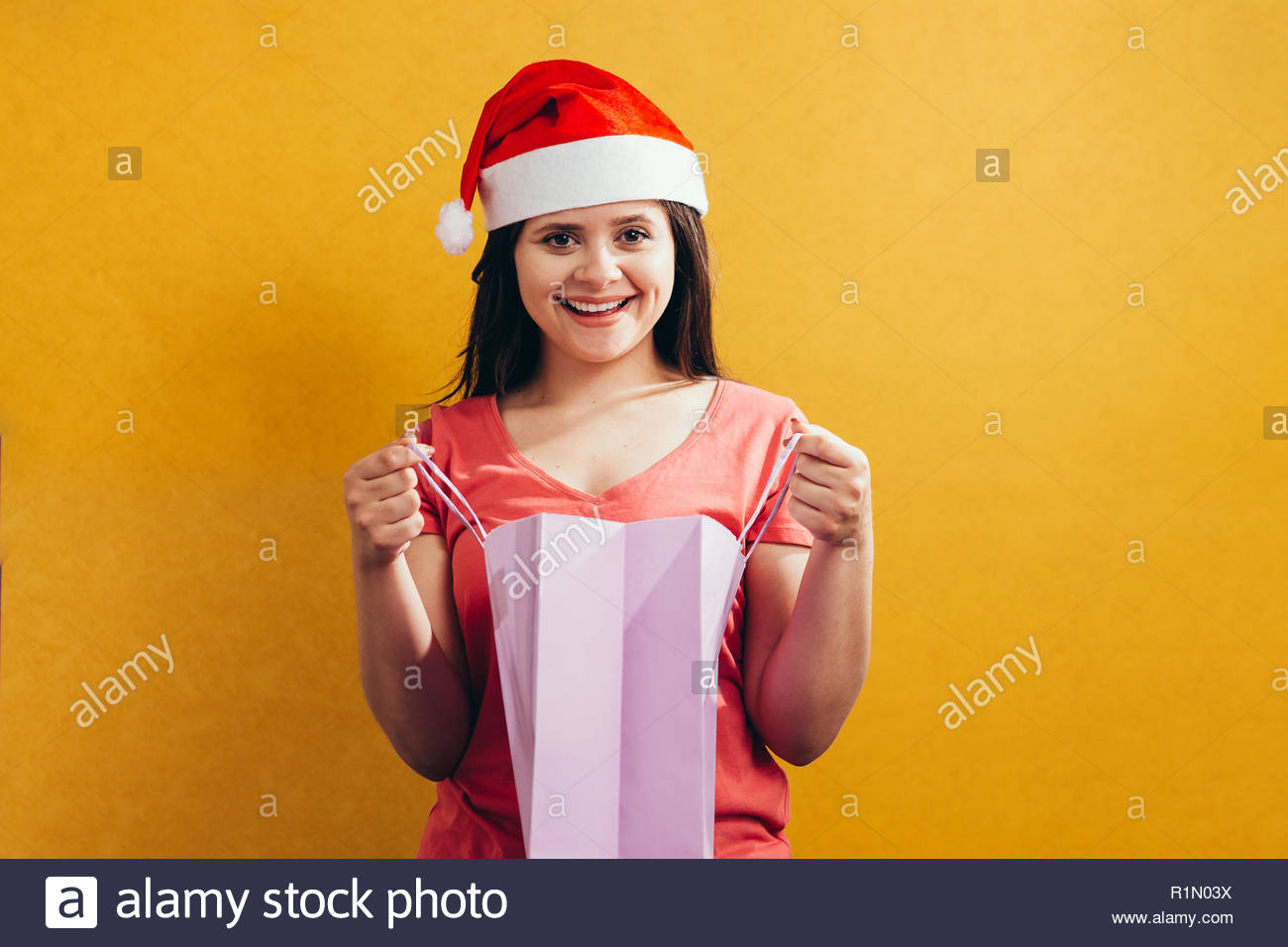 c6e97b19f713e Beautiful woman with a santa hat holding shopping bags on color background