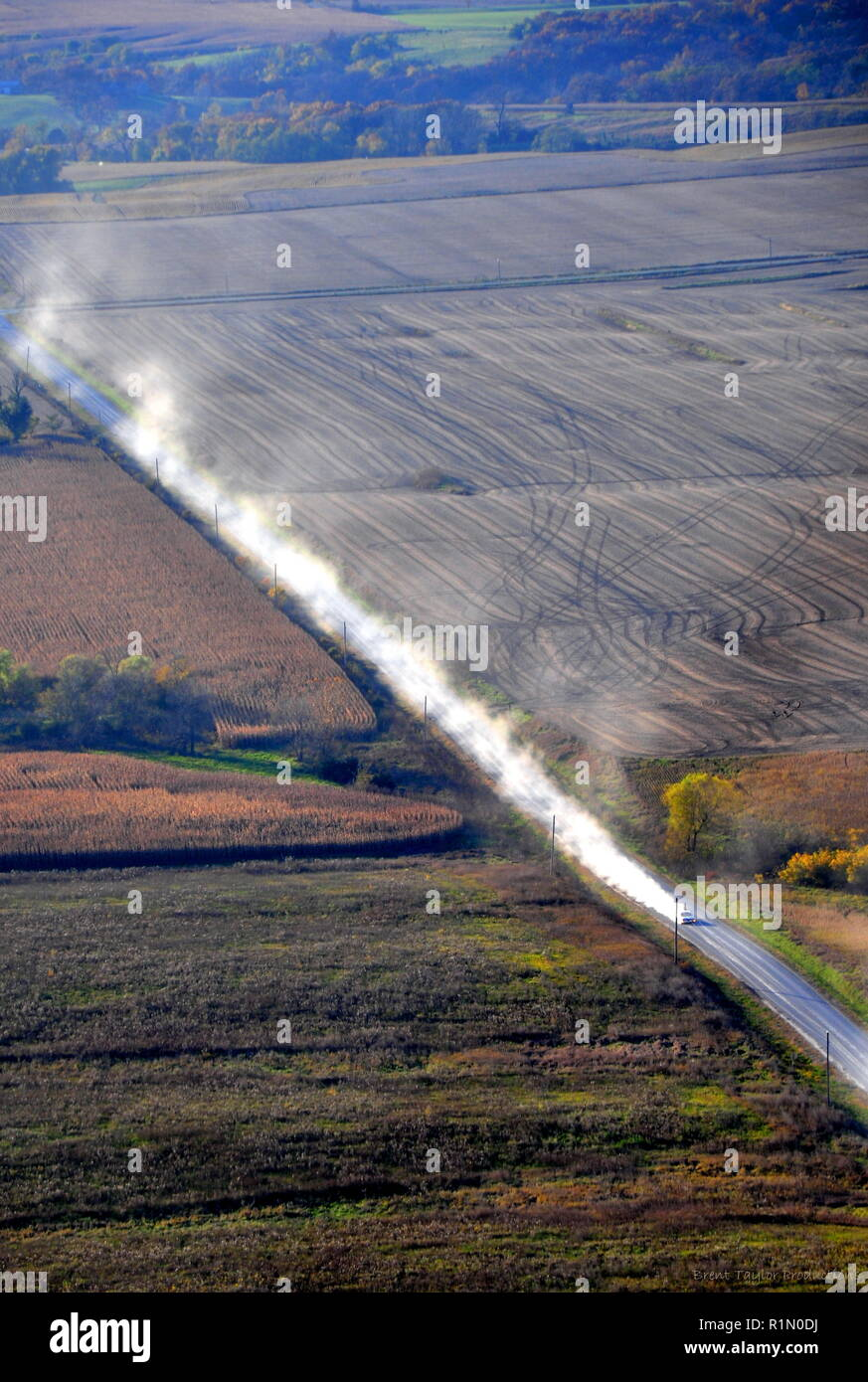 Aerial view of Midwestern farm fields and vehicle on a dusty gravel road - Stock Image