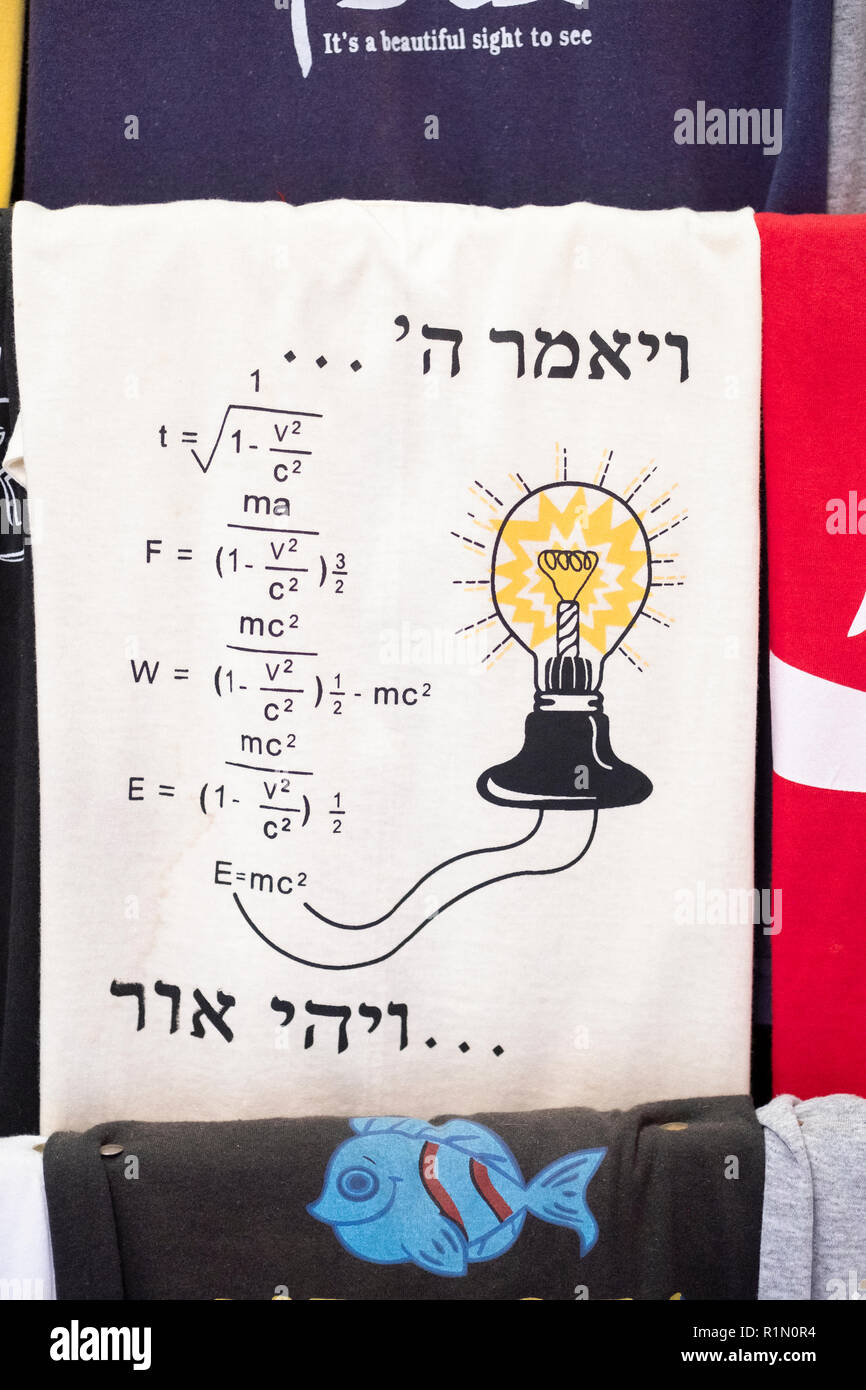 A t shirt for sale in the old City linking religion & scince. The Hebrew reads, 'God said...and there was light.' In Jerusalem, Israel. - Stock Image