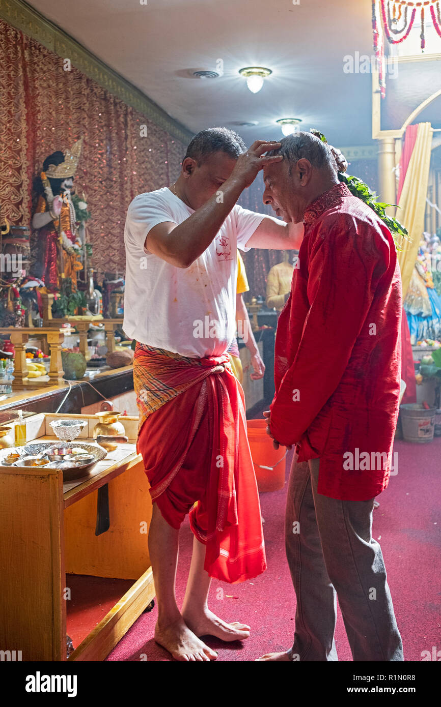 A male Hindu devotee gets a cleansing and blessing at a  Shakti Hindu temple in Queens, New York City. - Stock Image