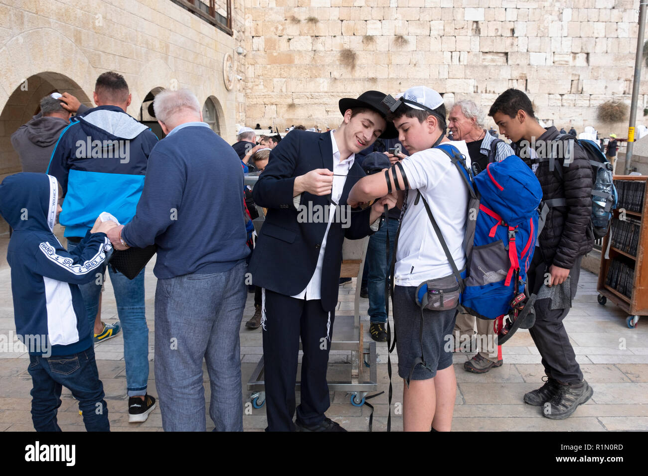 A young Lubavitcher Hasidic Jews helps another Jew put on tefillin at the Wailing Wall in Jerusalem, Israel. - Stock Image