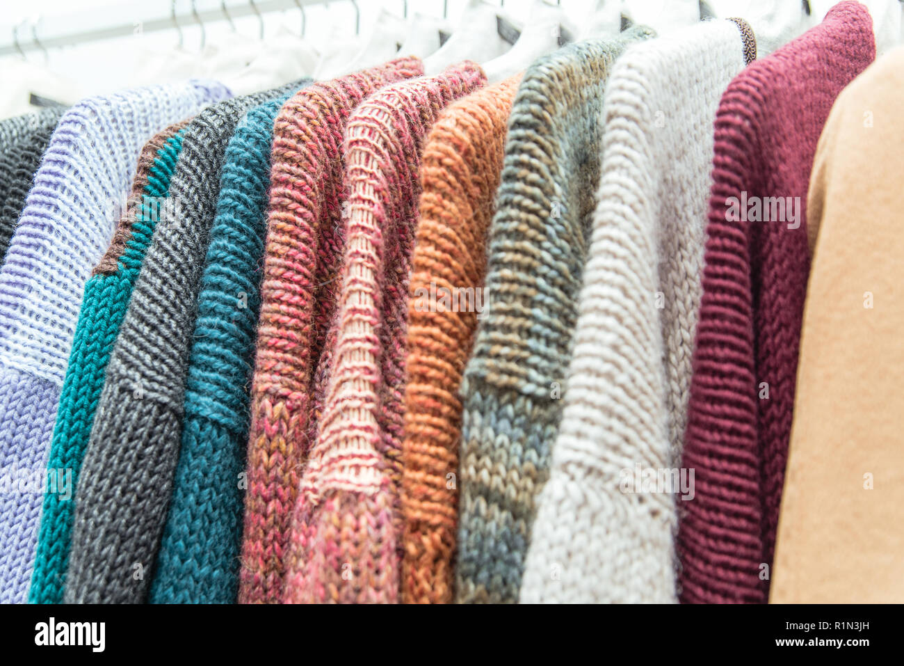 Nice warm colorful sweaters hang on hangers inside of a shopping mall. Beautiful  clothes for winter autumn season. Wool things for fall. Classic design. 74a439a91