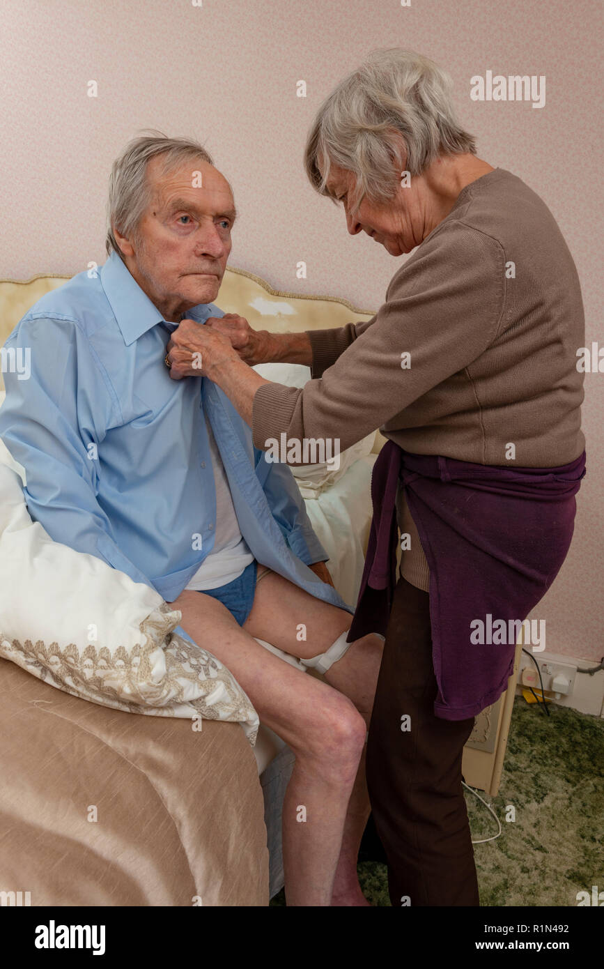 Sister helping her elderly brother to get dressed - Stock Image