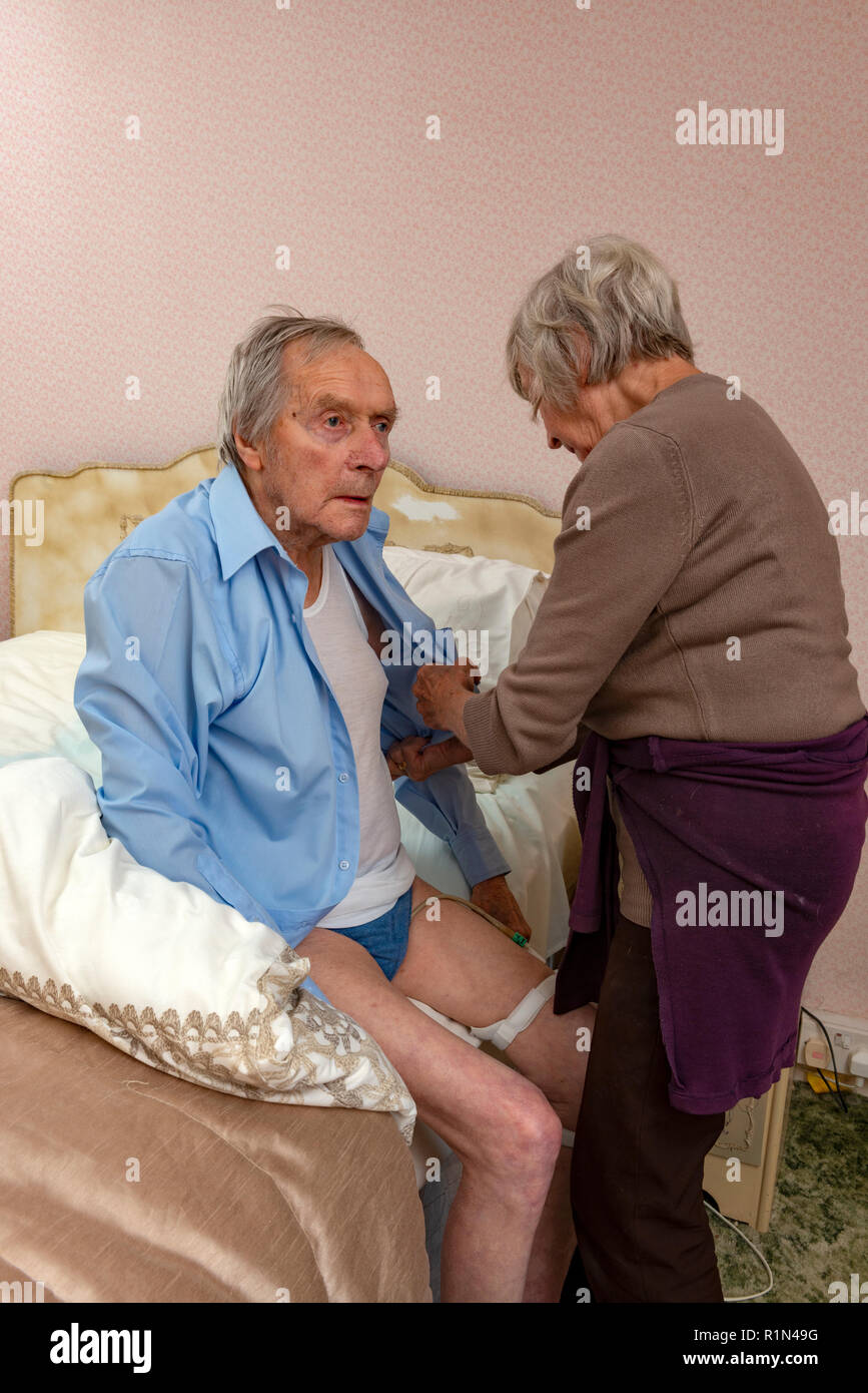 86-year old woman helping her 92-year old brother get dressed - Stock Image