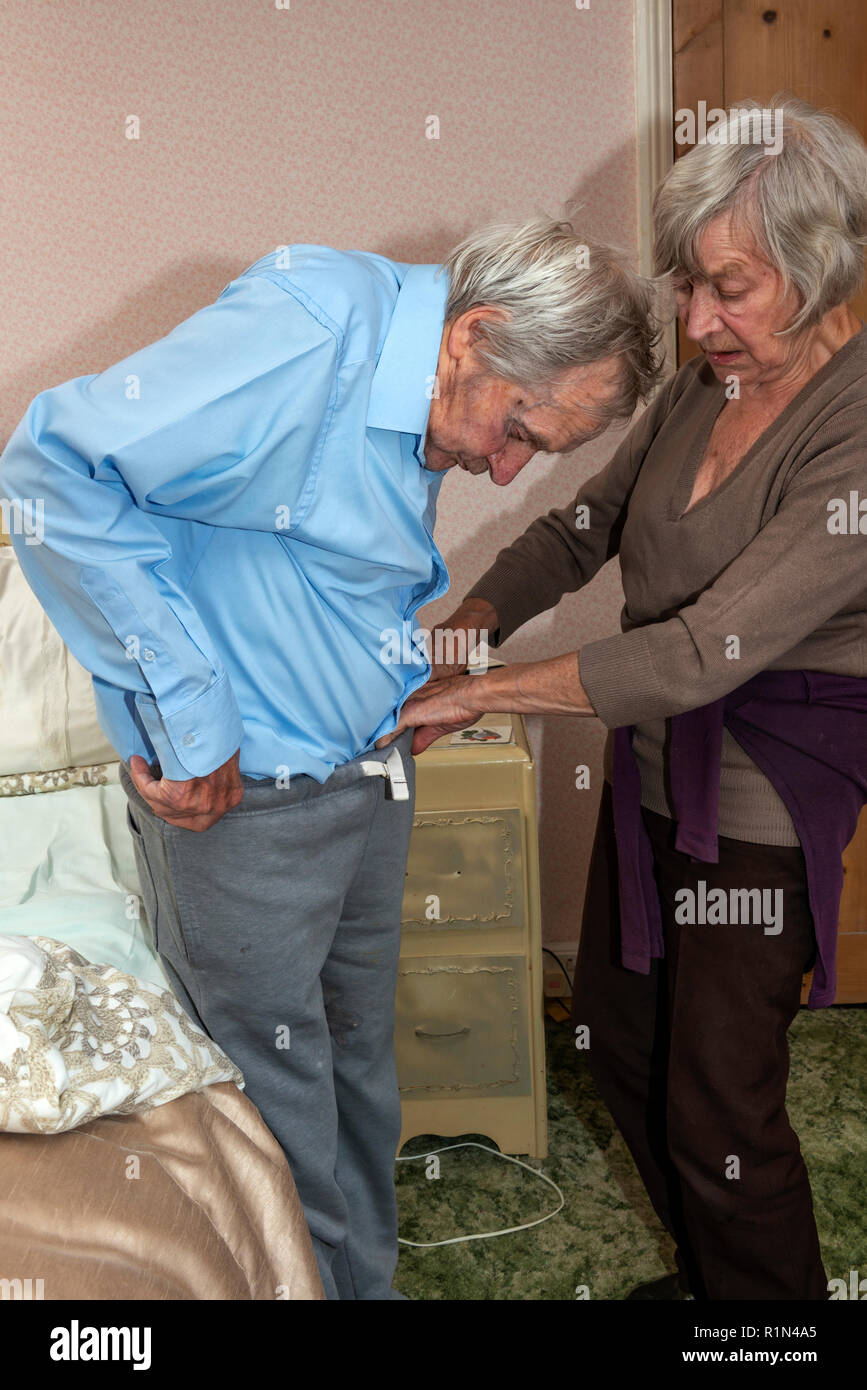 Elderly woman helping her brother to get dressed - Stock Image