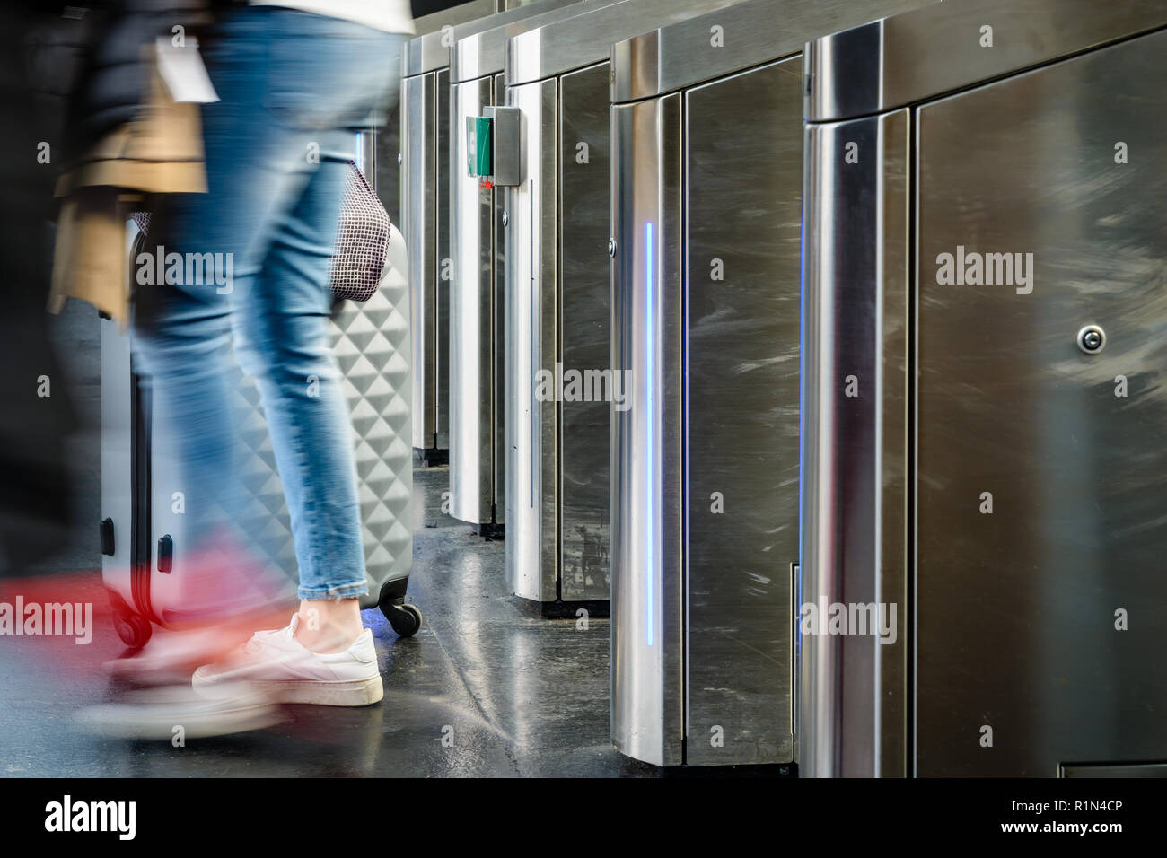 Side view of a woman with a rolling suitcase passing through stainless steel ticket gates in a public transportation station in Paris with motion blur - Stock Image