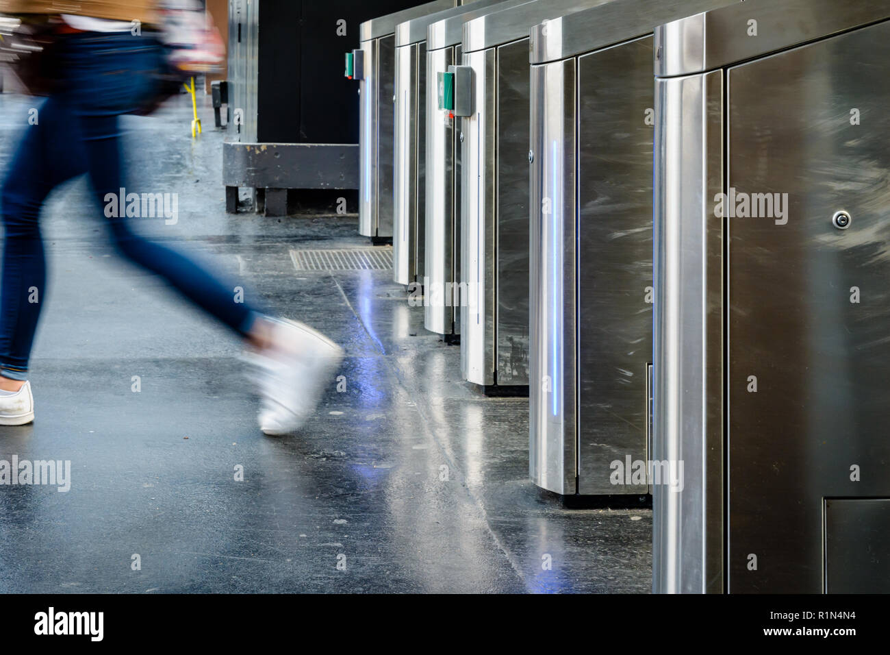 Side view of a young woman passing through stainless steel ticket gates in a public transportation station in Paris, France, with motion blur. - Stock Image