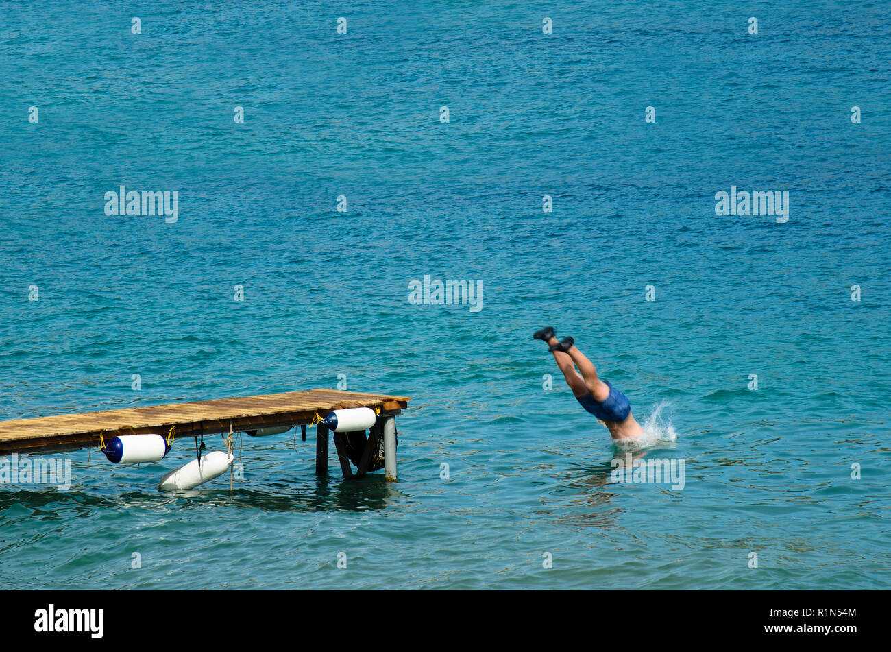 Man in a bathing suit dives into the sea from a wooden pier, wearing black rubber shoes Stock Photo