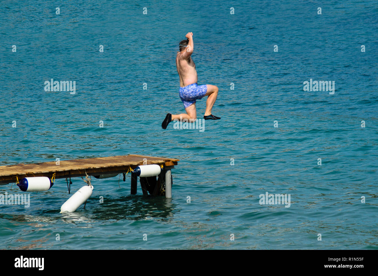 Man in swimsuit jumping into the sea from a wooden pier, wearing black rubber shoes Stock Photo