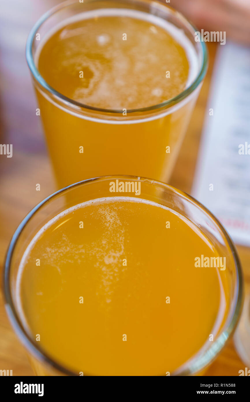 Close up of two tall glasses of beer on a table at a restaurant - Stock Image