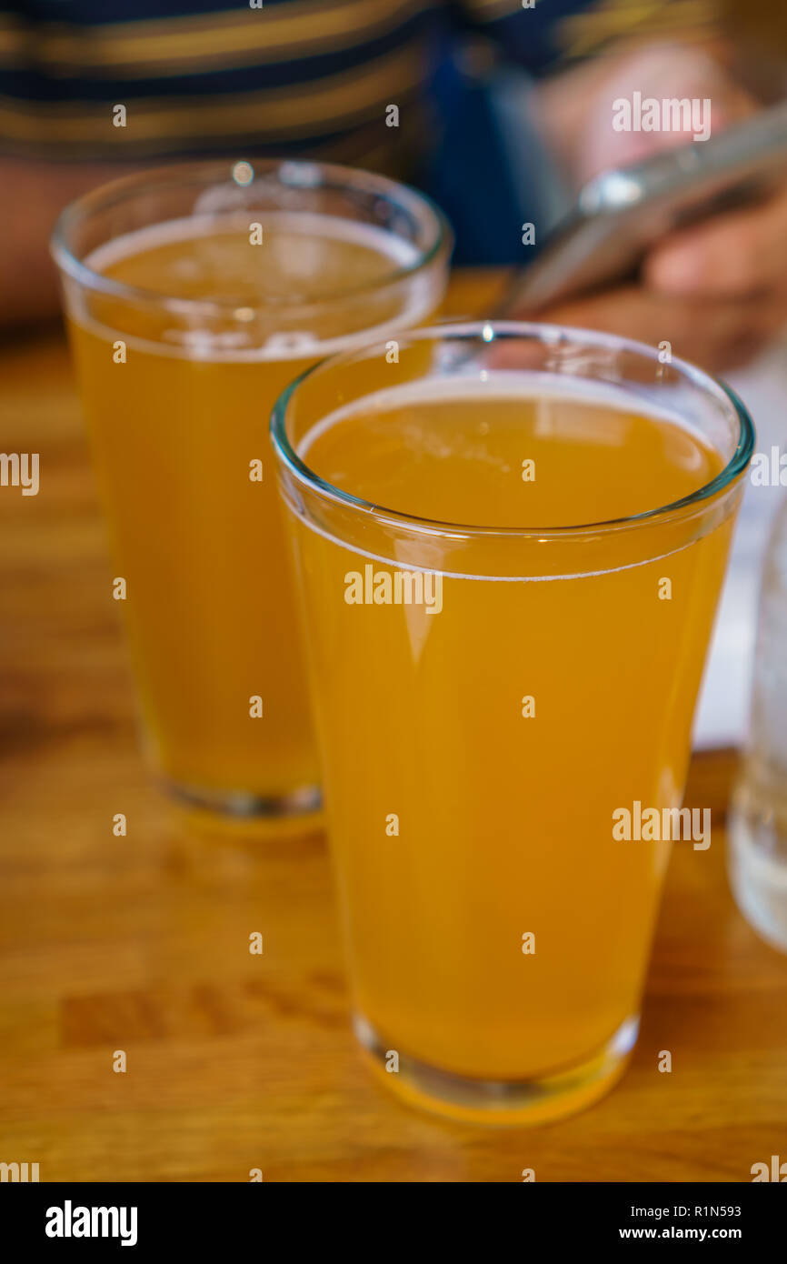 Close up of two tall glasses of beer on a table at a restaurant with person holding mobile phone in background - Stock Image