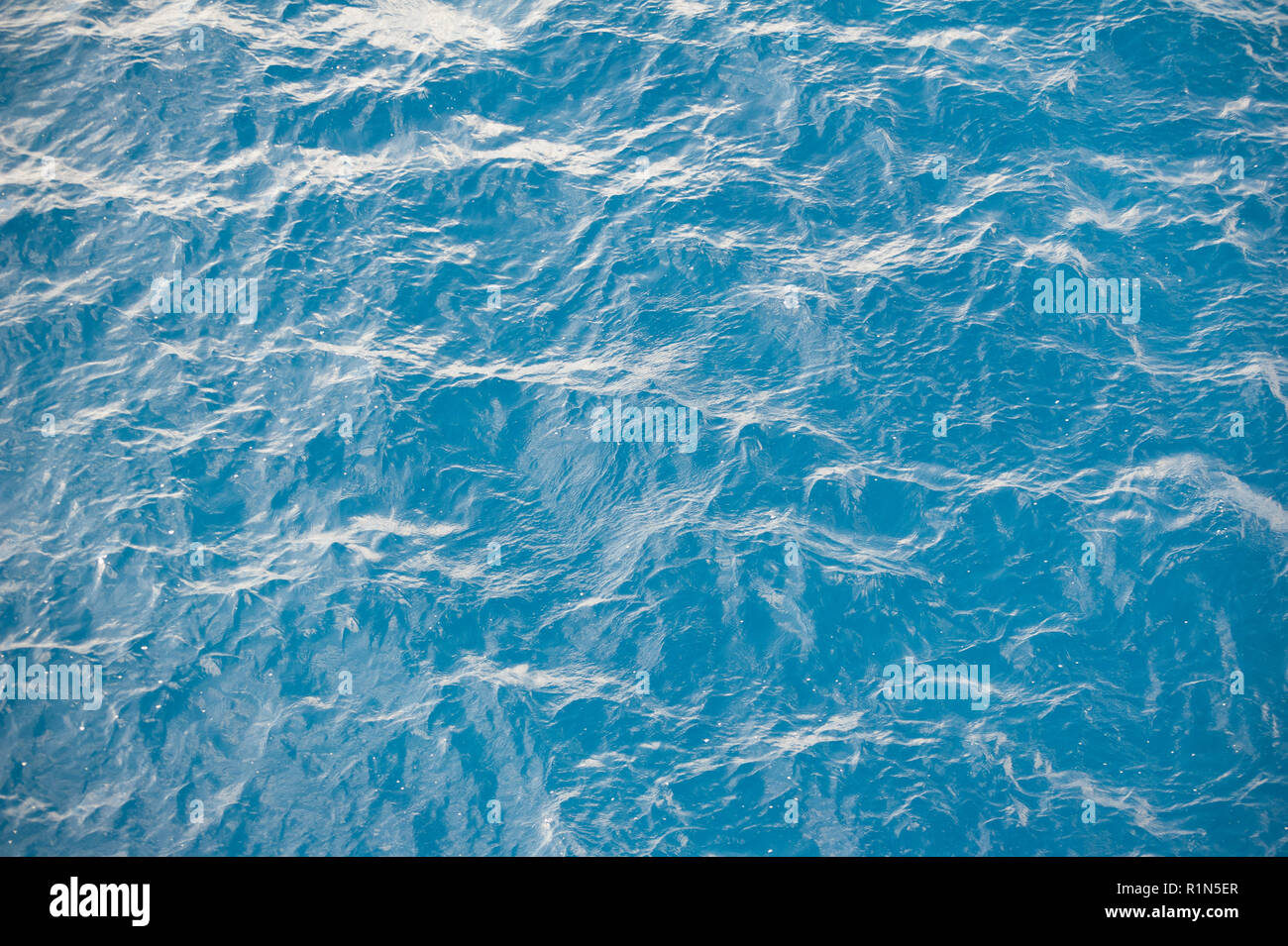 High angle blue ripple water background texture. Mediterranean sea waves on bright sunny day. - Stock Image
