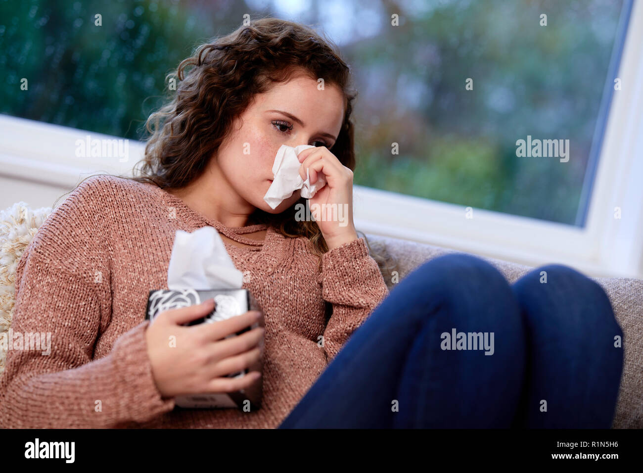 Woman with tissues blowing her nose - Stock Image