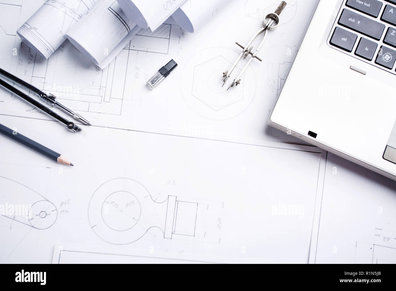 A notebook, a pencil, a compass and rolls with drawings on the table in the architect - Stock Image