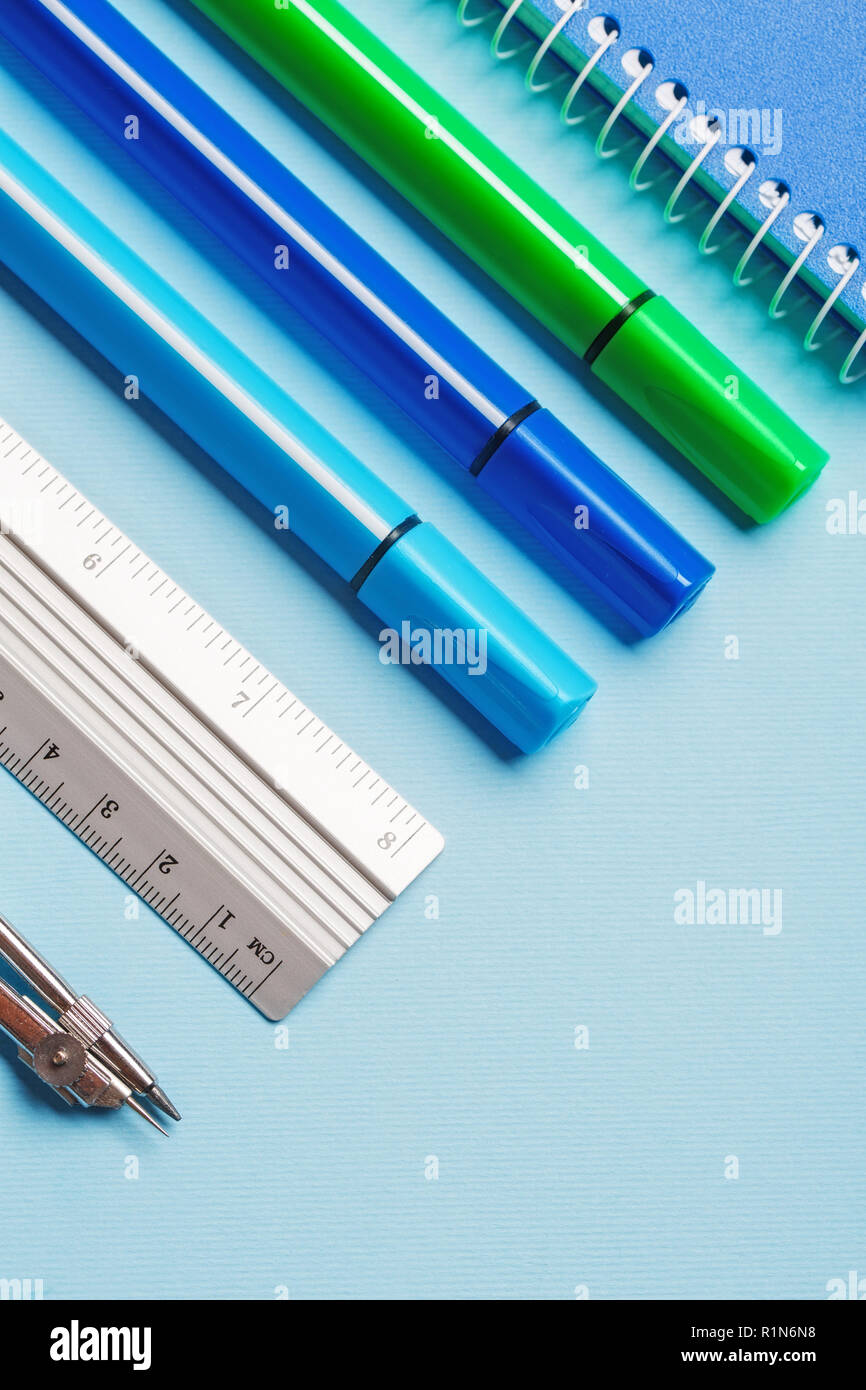 Markers, compasses, rulers and notebooks on a blue background - Stock Image