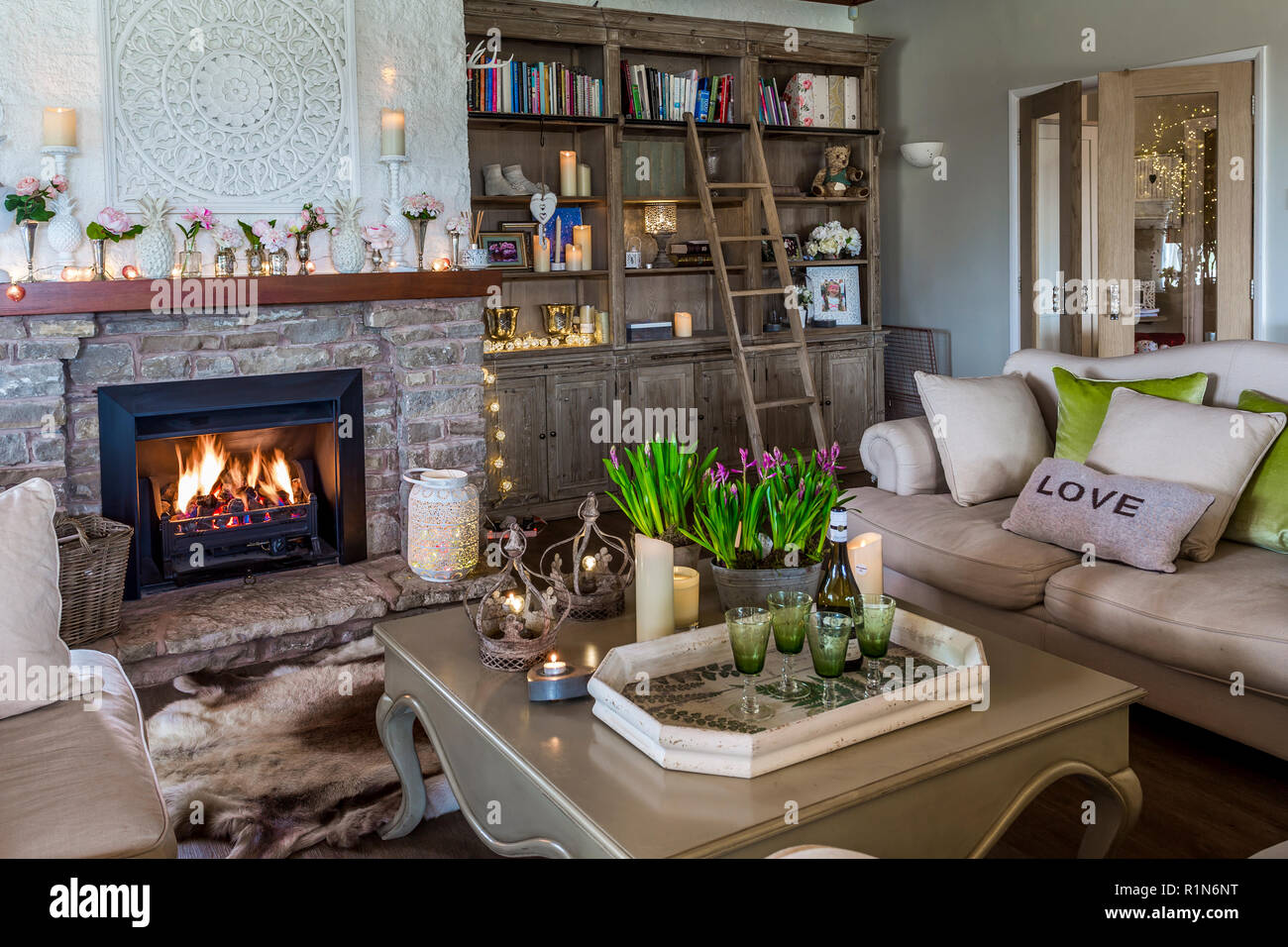 cosy sitting room with blazing fire - Stock Image