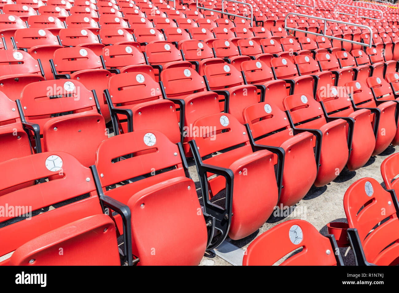 Rows of empty red bleacher seats in a stadium with numbers inside of baseball looking stickers. - Stock Image