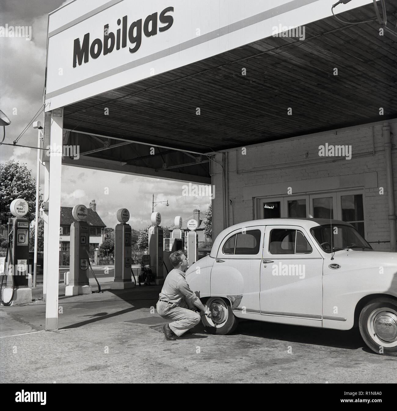 1950s, historical, the golden days of motoring, a service station sttendant checks the tyre pressure on an Austin car parked at the Mobilgas Ravenscroft Service Station, Great West Road, London, England, UK. - Stock Image