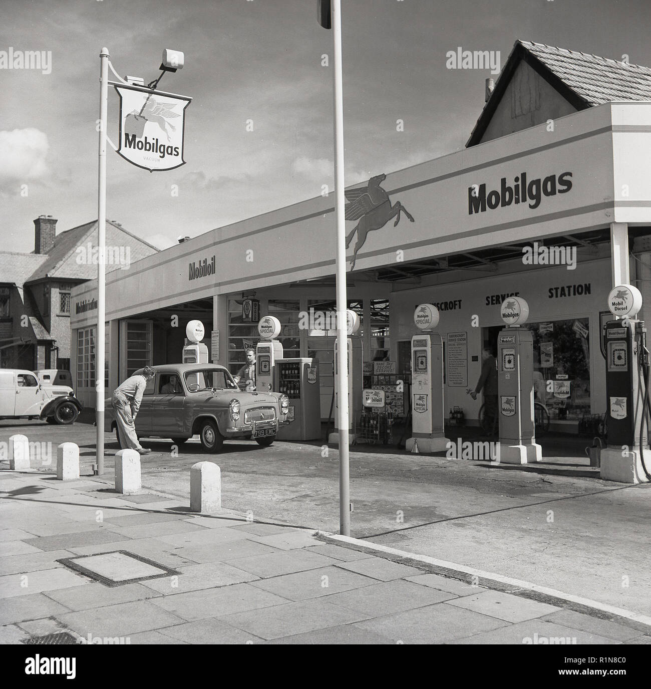 1950s, historical, the golden days of motoring, a service station sttendant talks to a driver of a car at the petrol pumps at the Mobilgas Ravenscroft Service Station on the Great West Road, London, England, UK. - Stock Image